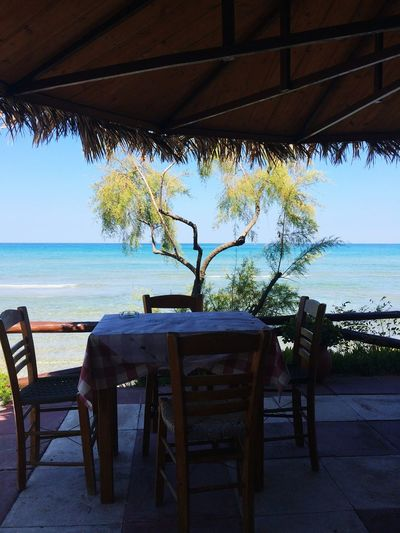 A Chair Clear Sky Beach Sea Horizon Over Water No People Water Day Tree Outdoors Beauty In Nature Sky Table traditional lunchtime view from a Greek Taverna....