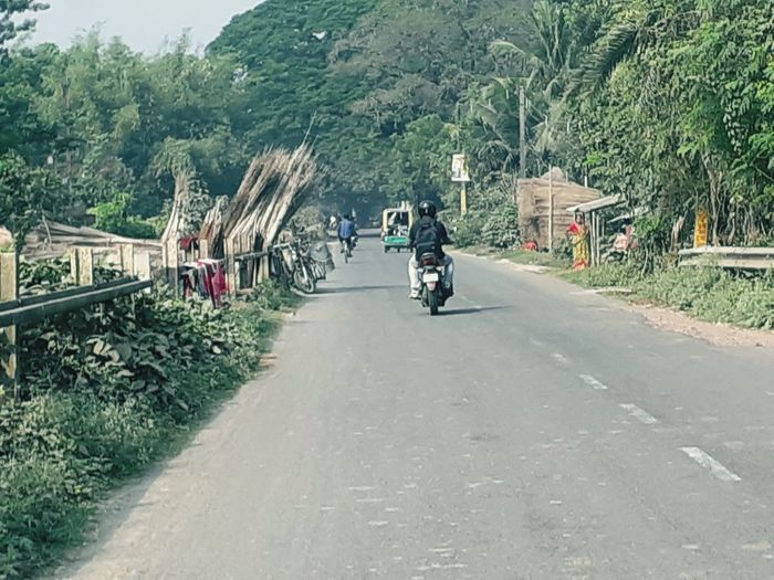 Rear view of man riding motorcycle on road in city