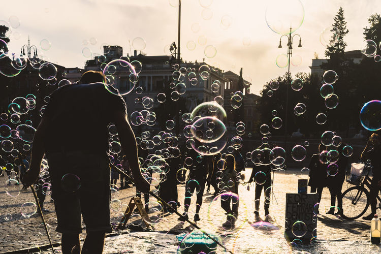 Real People Men Bubble Lifestyles Standing Nature Bubble Wand Day One Person Sky City Outdoors Full Length Leisure Activity Holding Occupation Shape Street Soap Sud