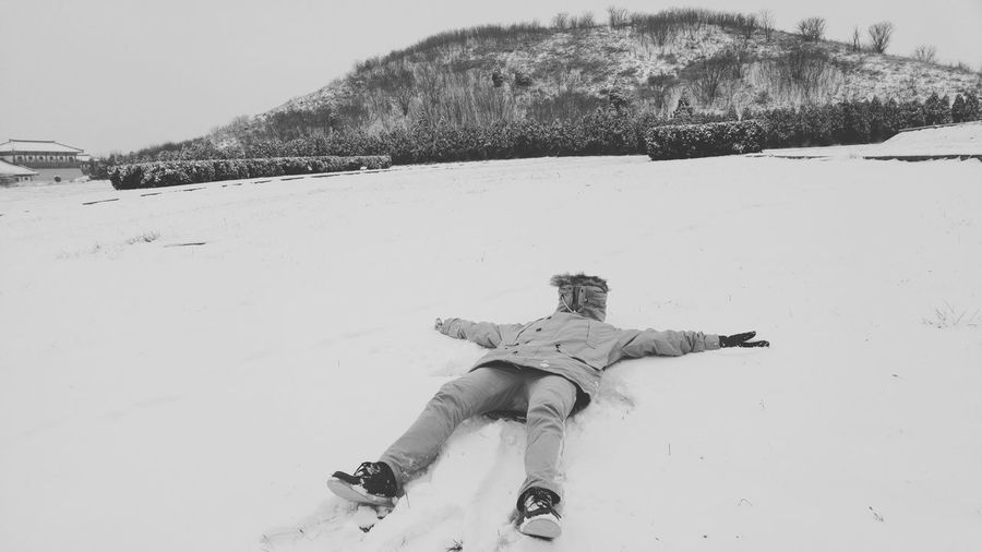Full Length Person Lying On Snow Covered Field By Mountain Against Sky