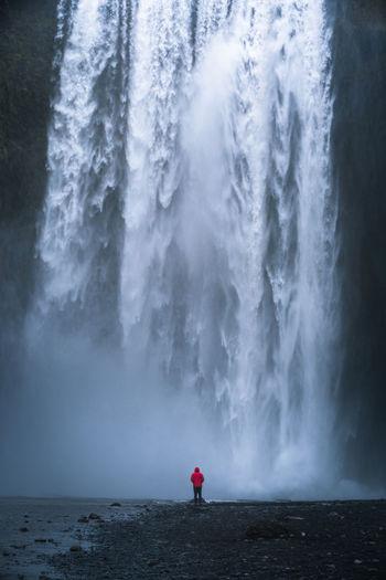 Rear view of man standing by skogafoss waterfall