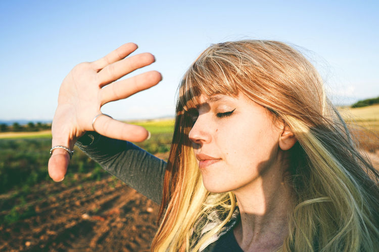 Young woman shielding eyes while standing at field against sky on sunny day