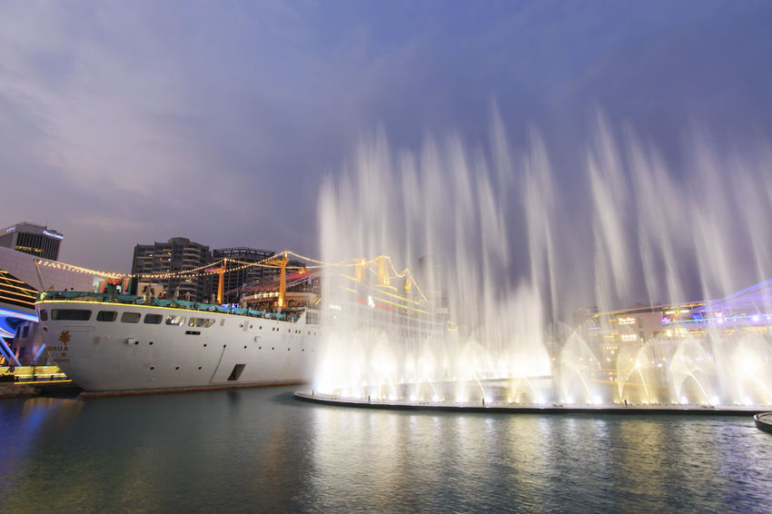 "Shenzhen, China - August 22,2015: Dancing Fountains in New Sea World Plaza, one of the landmark of Shenzhen, at sunset with the Minghua ship on its center. The ship was originally known as Anceevilla and was later renamed ""Minghua"" by the chinese who bought it. Anceevilla Architecture ASIA Beauty In Nature Built Structure China City Cloud Cloud - Sky Cloudy Dancing Fountain Guandong City Illuminated Nature No People Outdoors Reflection Scenics Shenzhen Shenzhen.China Sky Stock Market Travel Destinations Water Waterfront"