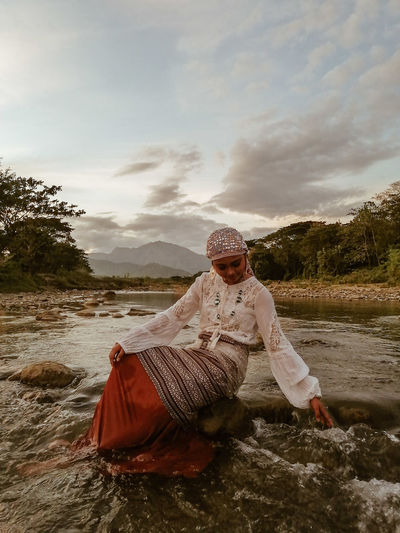 Young woman wearing traditional clothing sitting on rock amidst river