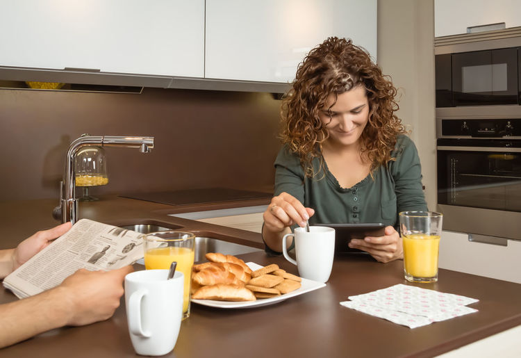 Happy smiling young girl reading news in a digital tablet at home breakfast while her husband read newspaper Young Woman Wife Two Together Thirties Technology Tablet Smiling Smile Relaxing Relationship People Orange Newspaper News Morning Meal Man Male Love Lifestyle Kitchen Juice Interior Indoors  Husband Home Healthy Happy Happiness Glass Girlfriend Girl Fruit Food Female Family Drink Digital Cup Couple Coffee Cheerful Caucasian Breakfast Boyfriend Adult 30s