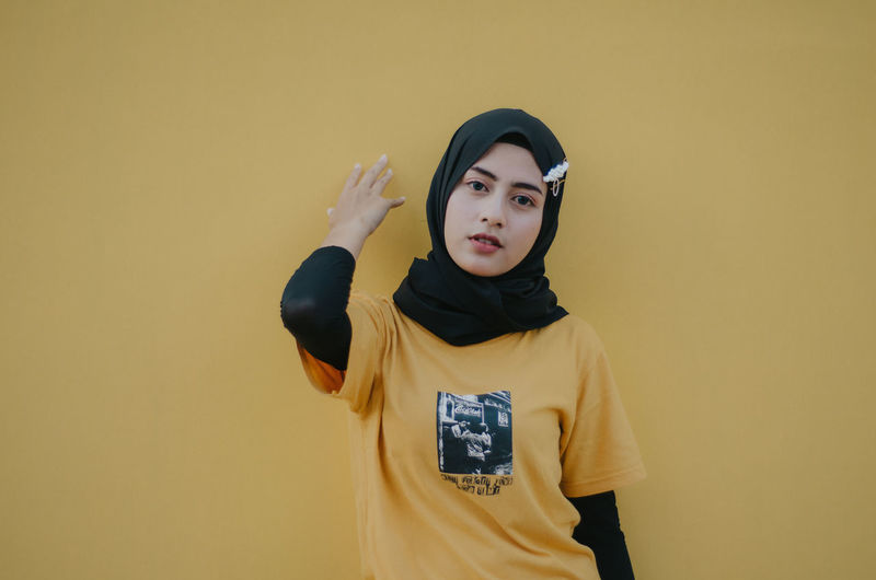 Portrait of woman wearing hijab standing against yellow wall