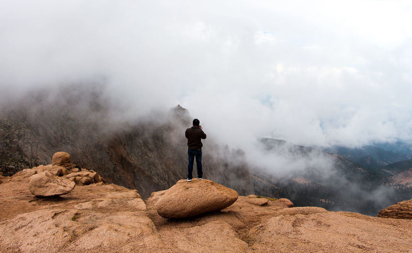 Rear view of man photographing mountain landscape against cloudy sky