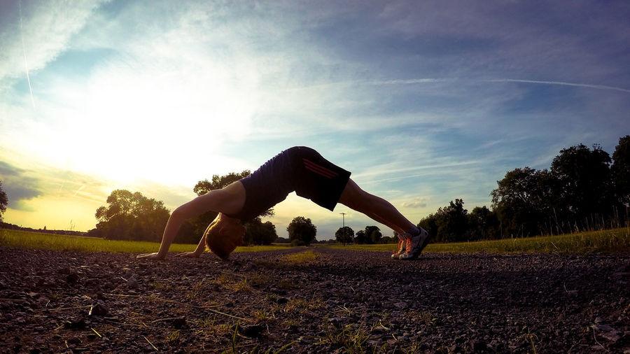 Full Length Of Man Exercising On Road During Sunset