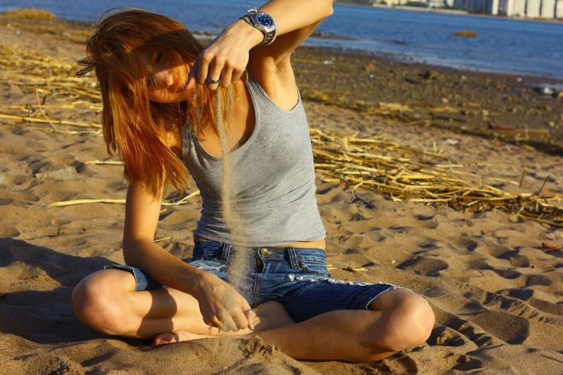 Full Length Of Young Woman Playing With Sand While Sitting On Shore At Beach