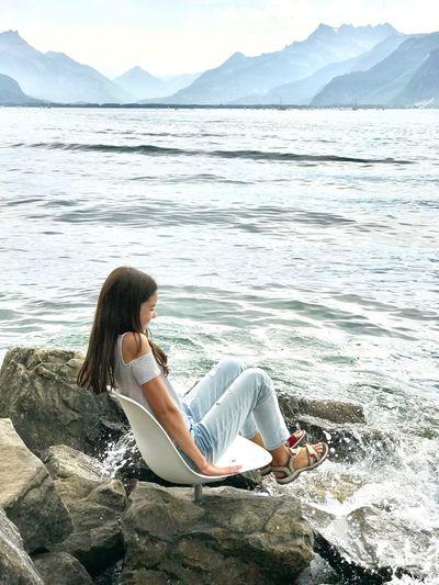 Girl sitting on shore against sea