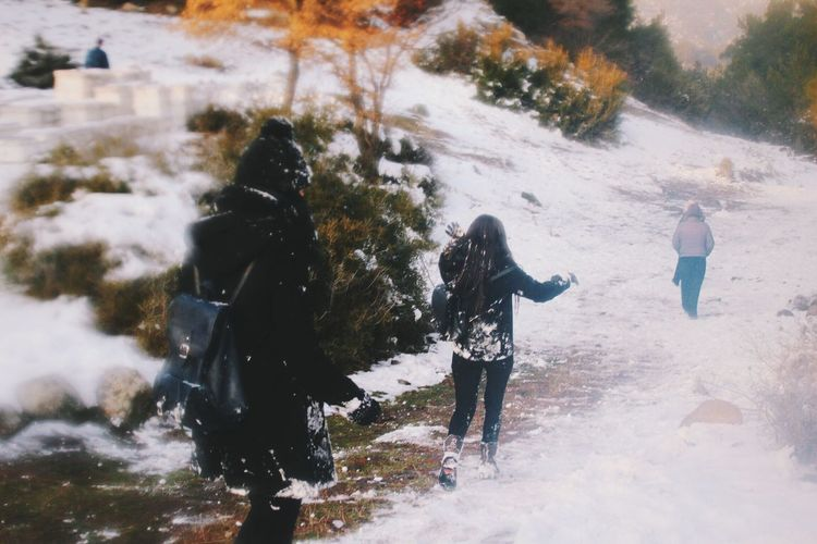 People on snow covered landscape during winter