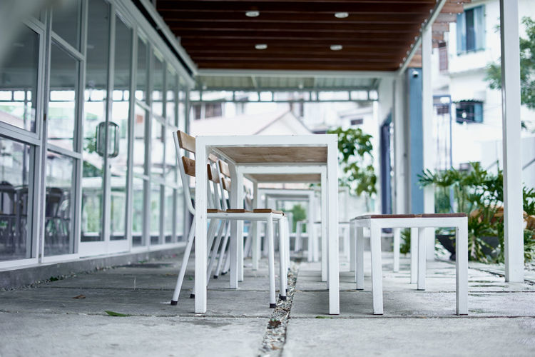 Empty chairs and tables in yard against house