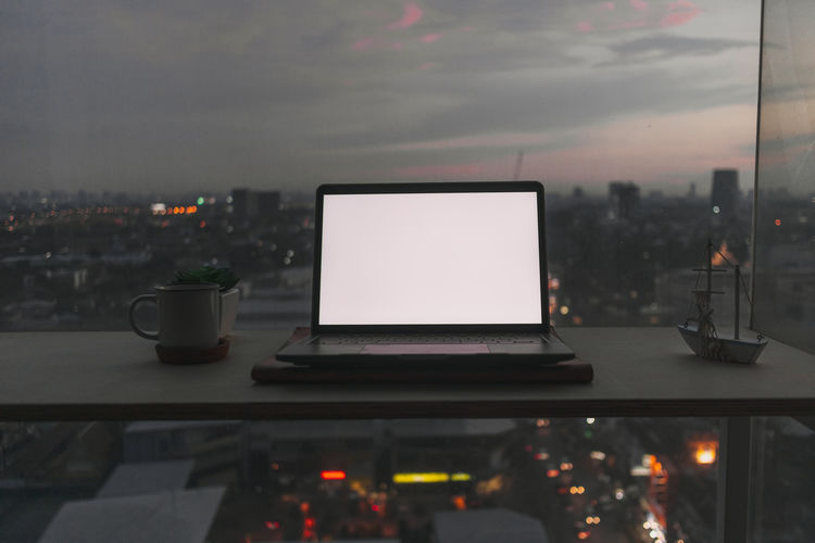 Illuminated city seen through glass window at night