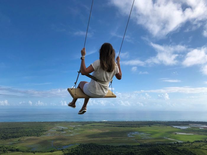 Rear view of woman on swing over landscape