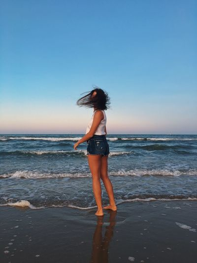 Full length of woman standing on shore at beach against clear sky