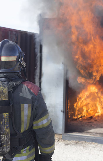 Rear view of firefighter working outdoors