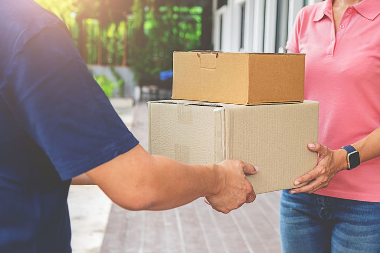 Midsection of delivery person giving boxes to woman outdoors