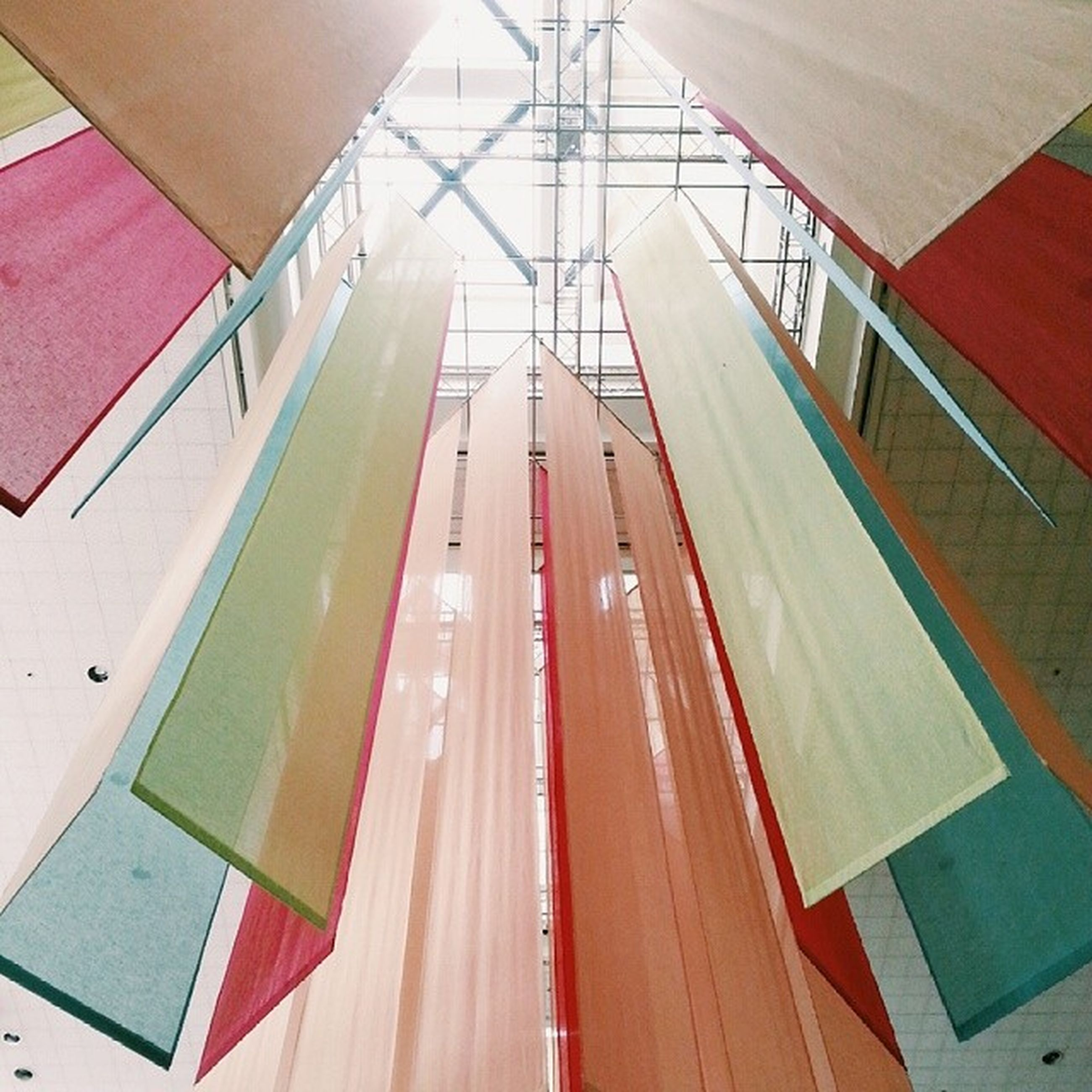 indoors, empty, red, absence, high angle view, no people, pattern, built structure, in a row, multi colored, architecture, diminishing perspective, modern, ceiling, close-up, day, steps, railing, table, seat