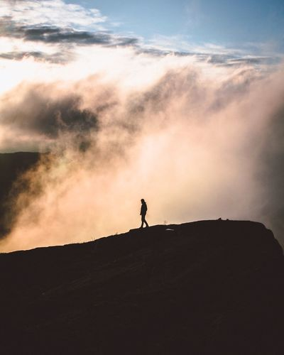 Silhouette man walking on mountain against cloudscape