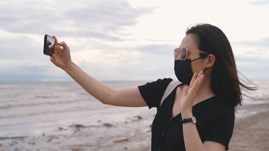 Midsection of woman photographing with mobile phone at beach