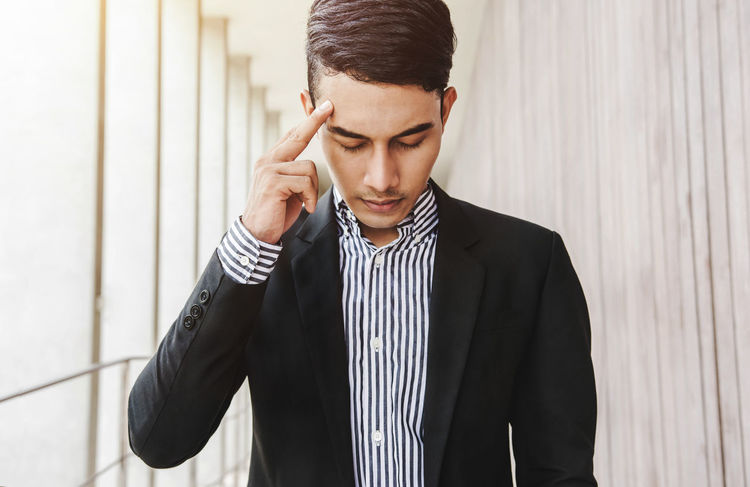 Businessman thinking seriously concept, finger on head and closed eyes, Front view Adult Adults Only Business Business Finance And Industry Businessman Close-up Day Disappointment Front View Indoors  Looking Down Men One Man Only One Person Only Men People Real People Seroius Standing Striped Tensed Think Thoughtful Young Adult Young Men