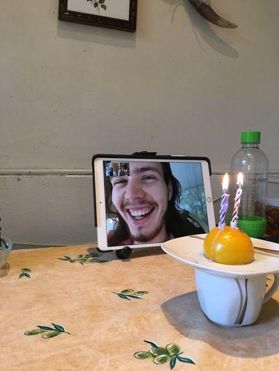 Portrait of smiling young man using smart phone on table