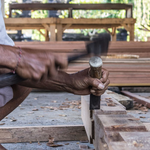 Cropped hands of carpenter with wood working outdoors
