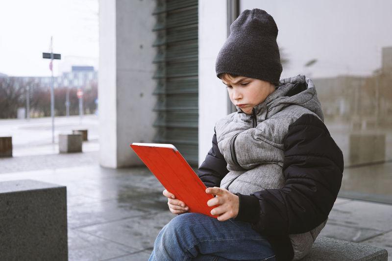 Boy Using Digital Tablet On Seat