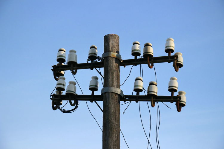 Low angle view of telephone pole against clear blue sky