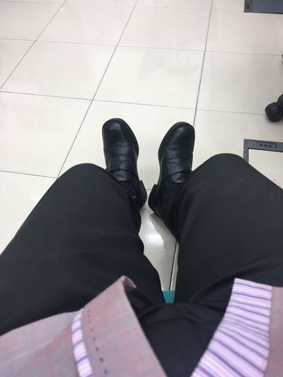 Low Section Human Leg Black Color High Angle View Indoors  Shoe Standing Tiled Floor Relaxation Real People Human Body Part Legs Crossed At Ankle One Person Men Day One Man Only