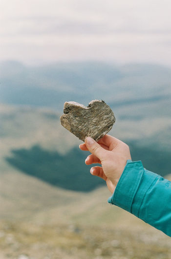 Cropped hand holding heart shape stone against mountains