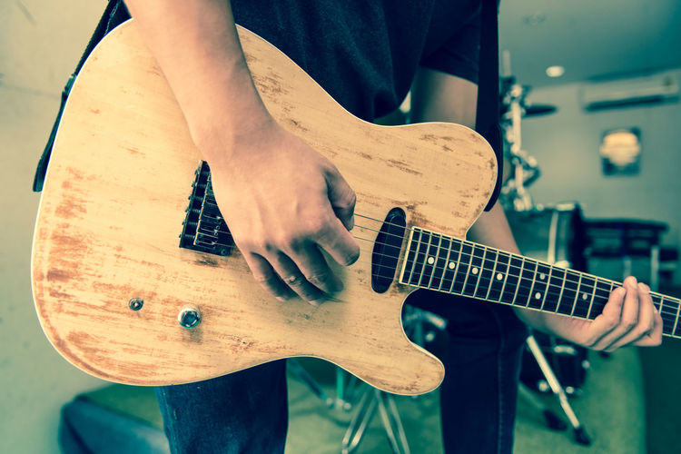 Midsection of musician playing guitar