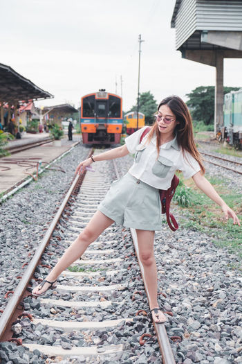 Full length of woman on railroad tracks