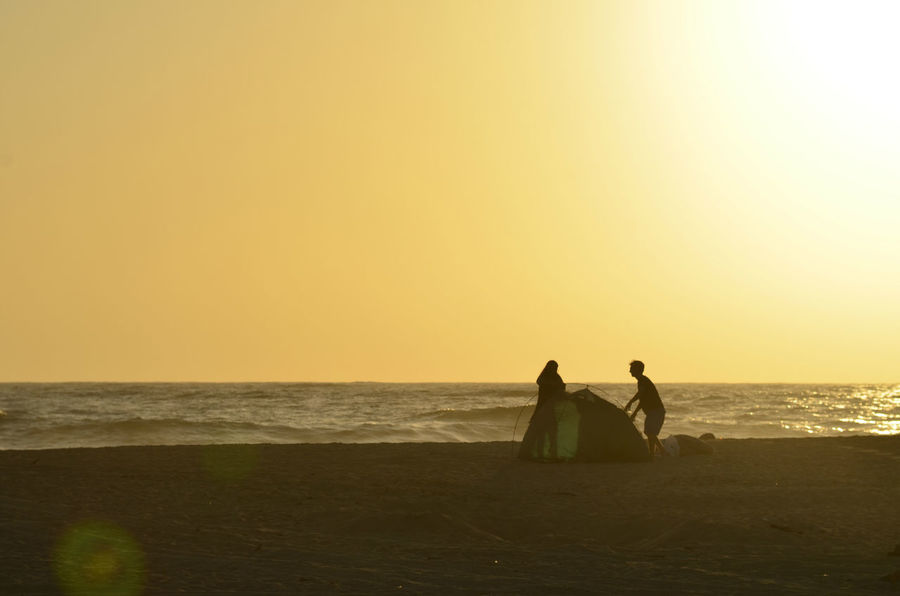 man and woman young couple in silhouette at dusk on ocean beach jointly working together to construct their camping tent for the evening in Baja California Sur, Mexico Silhouettes Beach Beauty In Nature Camping Tent Cooperation Couple - Relationship Dusk Horizon Horizon Over Water Leisure Activity Men Outdoors Positive Emotion Process Progress Putting Up A Tent Real People Scenics - Nature Sea Sky Step By Step Sunset Two People Water Working Together