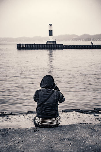 Rear view of person photographing lake while sitting on pier