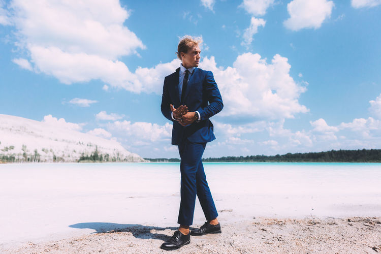 Full Length Of Man With Curly Hair Wearing Suit While Standing At Beach Against Sky