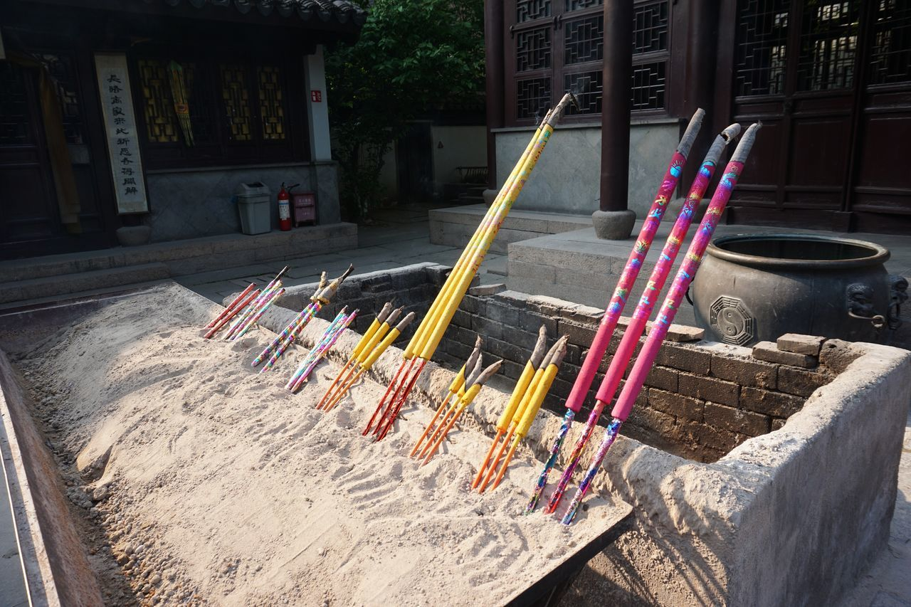 Close-Up Of Multi Colored Sticks On Sand
