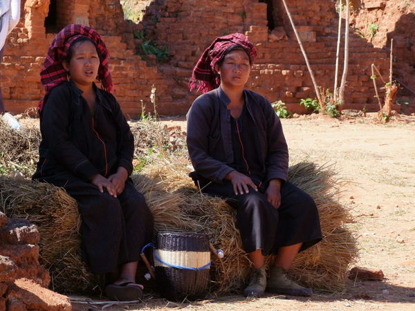 Two Shan Women Resting on Straw Bundles Composition Full Frame Inle Lake Kakku Making A Living Myanmar Outdoor Photography Resting Resting Place Resting Time Shan State Shan Women Sunlight And Shadows Tourism Tourist Attraction  Tourist Destination Traditional Clothing Two Women