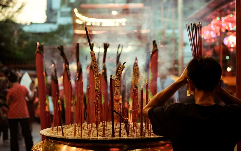 Religion Spirituality Incense Scented Burning Place Of Worship Tradition Adult Cultures Smoking - Activity People Travel Destinations Human Body Part Ash Outdoors One Person Day Adults Only Only Women Young Adult Chinese New Year