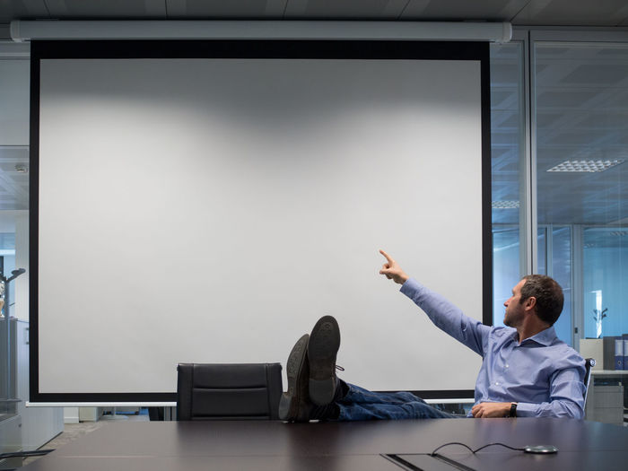 Businessman pointing towards projection screen while sitting in board room at office