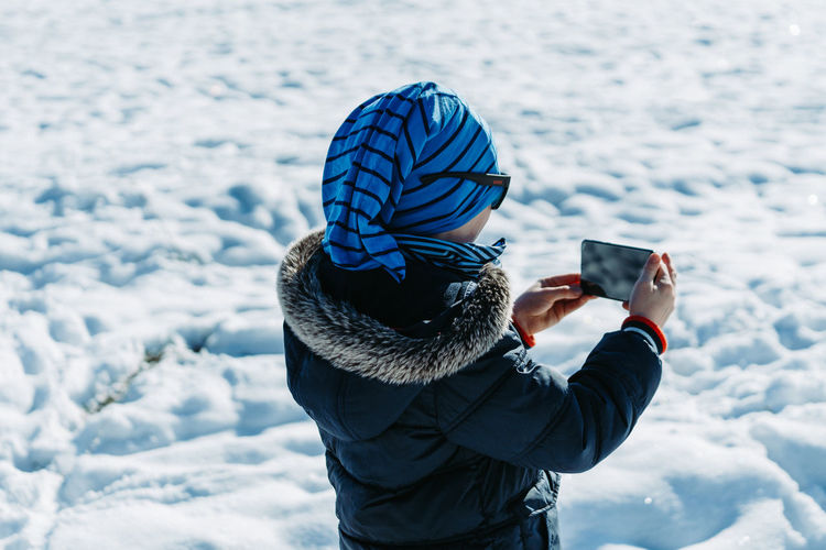 Man photographing with mobile phone in snow