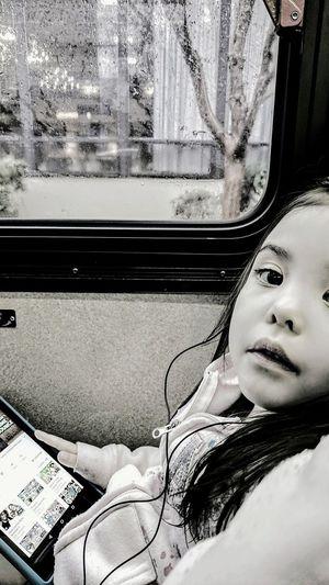 Close-up of girl sitting on train window