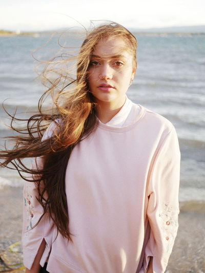 Portrait of beautiful young woman standing at beach