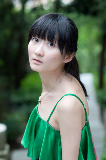 Portrait of young woman wearing green sleeveless top