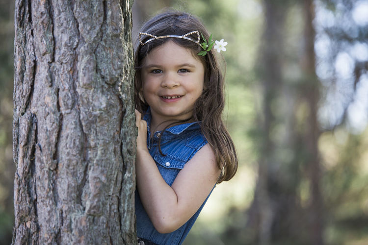Portrait of smiling girl against tree trunk