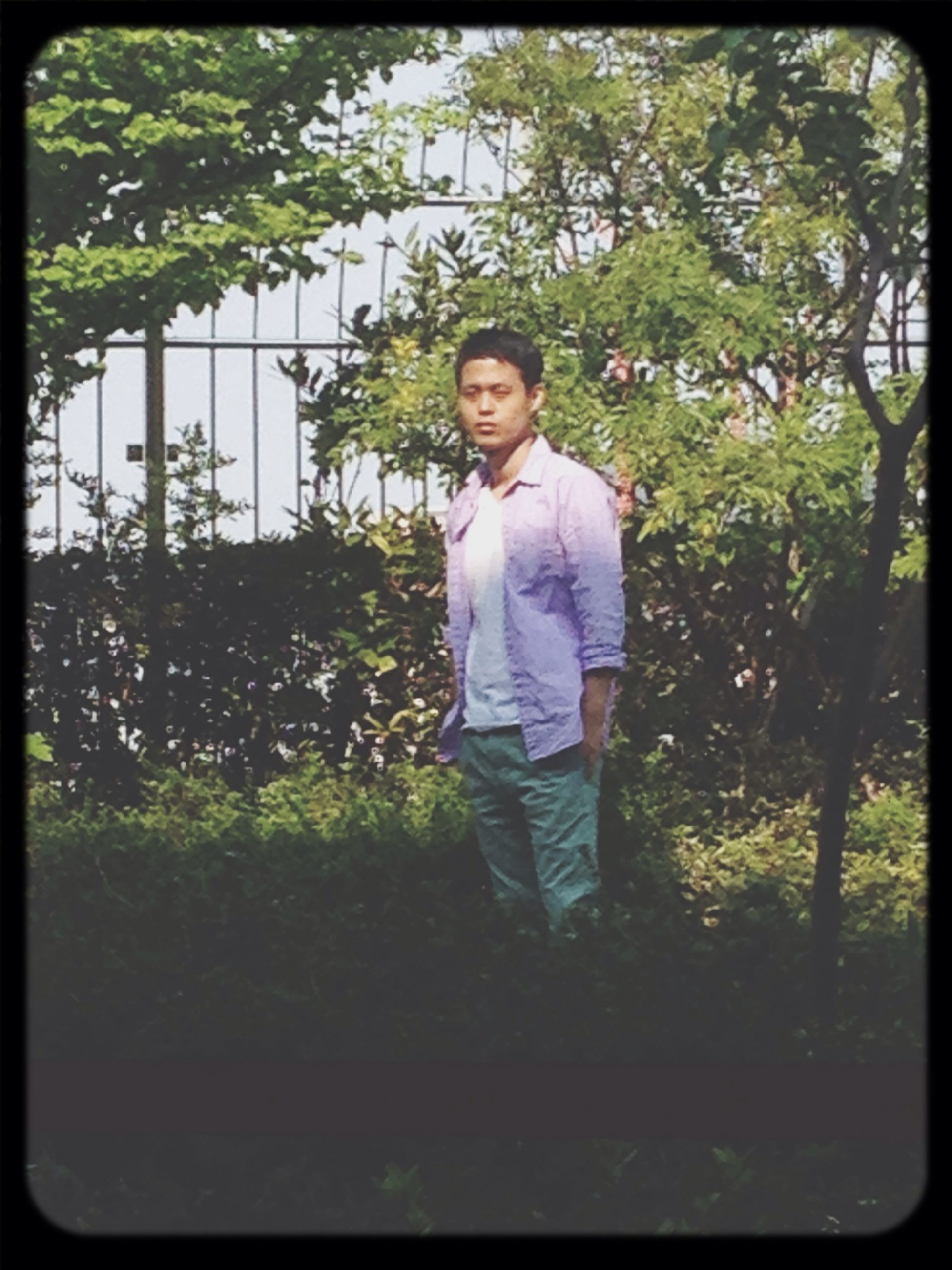 person, looking at camera, portrait, casual clothing, transfer print, tree, lifestyles, standing, front view, full length, leisure activity, smiling, young adult, auto post production filter, elementary age, childhood, plant, park - man made space