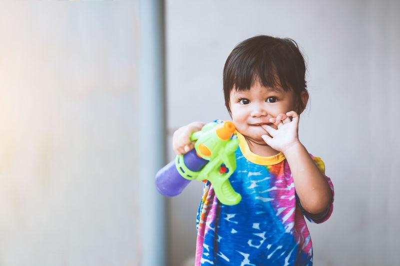 Portrait of cute baby girl holding squirt gun