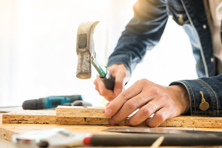 Midsection of carpenter with hammer working on bench