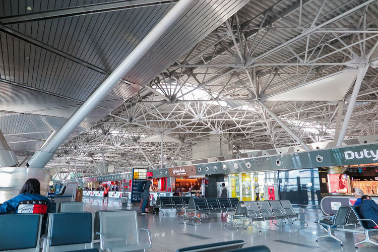 Фотобанк Stockxpert Indoors  Architecture Built Structure Group Of People Real People Men Travel Modern Industry Day Adult Transportation Crowd Incidental People People City Women Airport Ceiling Waiting The Traveler - 2019 EyeEm Awards