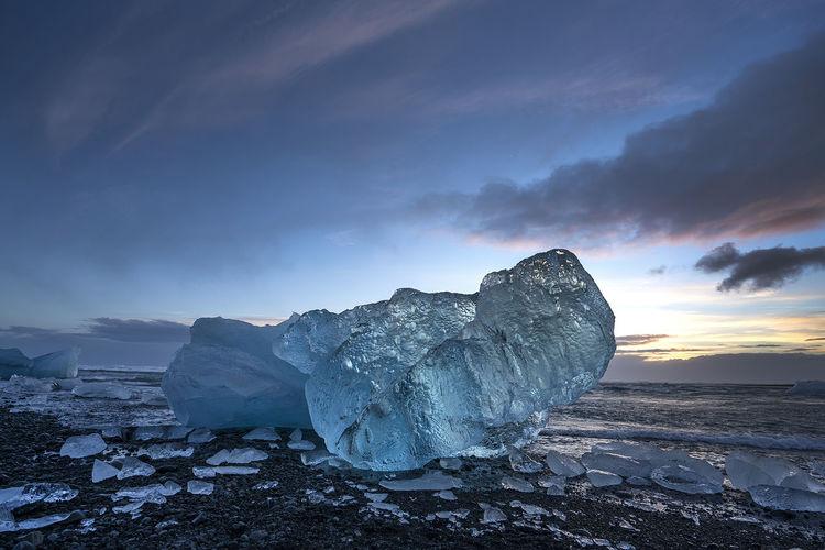 Iceberg at beach against sky during sunset